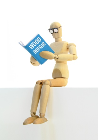 Wooden manikin sitting down reading a book on wood repair.