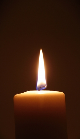 flame like: Vertical burning candle in the dark