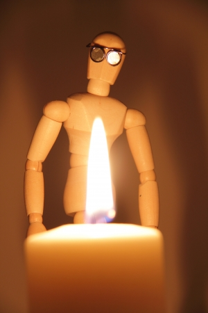 endangerment: Wooden artist manikin with glasses looking at a flame on a burning candle