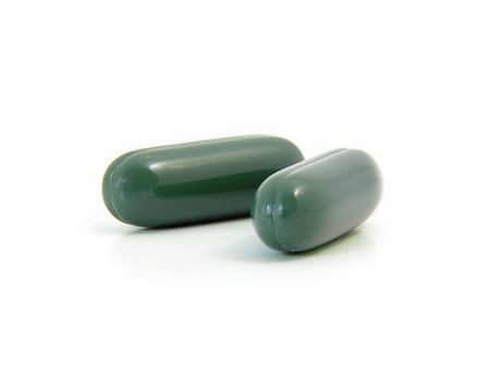 Two green tea pills isolated on white. 版權商用圖片