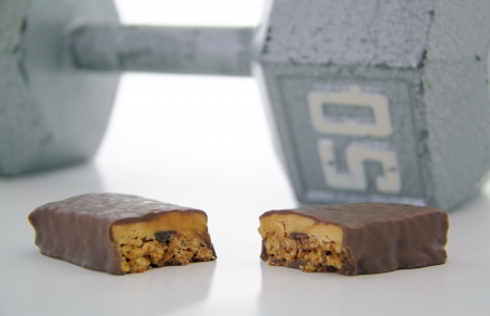 Cut protein bar with 50 pound weight in the background. Stock fotó