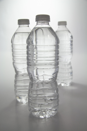 Vertical shot of three plastic bottled waters. Stock Photo