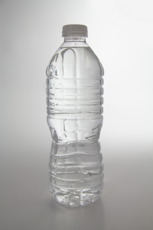 Vertical shot of a single plastic bottle of water.
