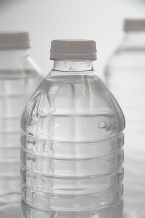 distilled water: Tiro vertical de tres botellas de pl�stico de agua.