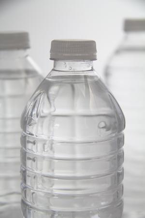 distilled water: Vertical shot of three plastic bottles of water.