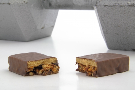 Broken protein bar with large dumbbell in the background