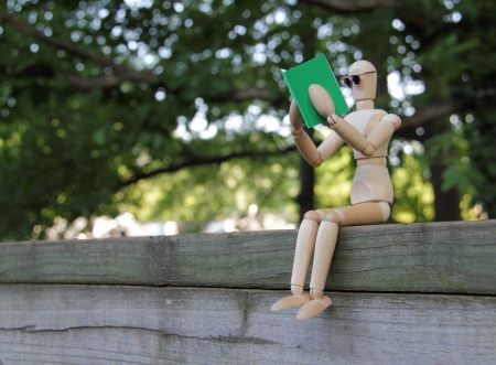 glass fence: Wooden artist manikin sitting on a wooden fence and reading a green book