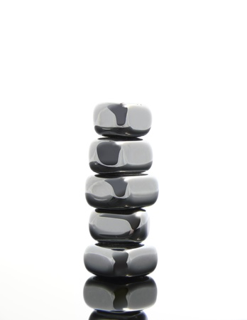 reflective: Silver, reflective, metallic stones stacked on a glass table