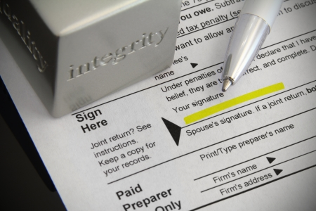Tax form with signature field highlighted, ink pen, and an integrity paper weight