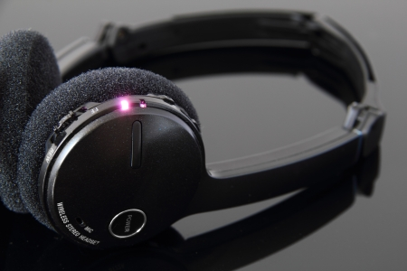 Rechargeable stereo bluethooth headphones with charging light on.