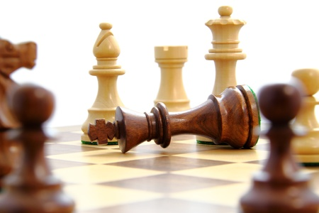 chess board: Check mate,fallen king surrounded by opponent.