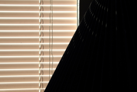 Window blinds and a lamp shade in a dark room.
