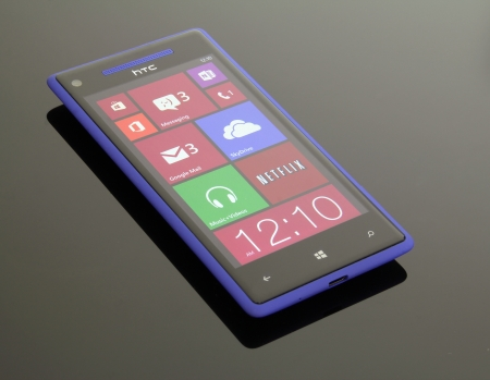 windows: A blue Windows Phone 8 on reflective; glass table. Editorial