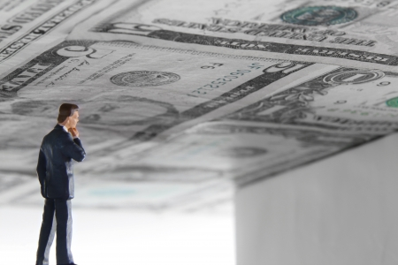 inquisitively: Business man looking inquisitively with a ceiling made of money overhead  Stock Photo