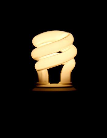 Electrified fluorescent light bulb over black.