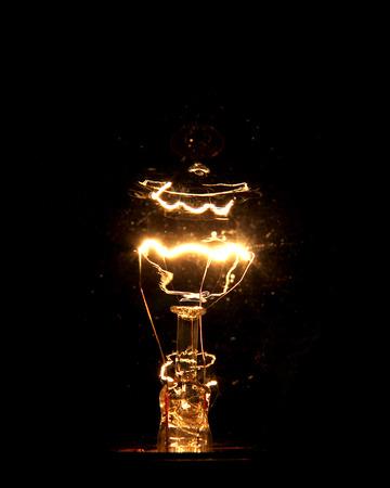 Electrified light bulb filament over black.