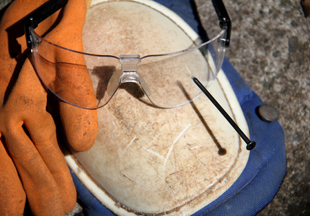 safety goggles: Safety goggles resting on other safety equipment outside. Stock Photo