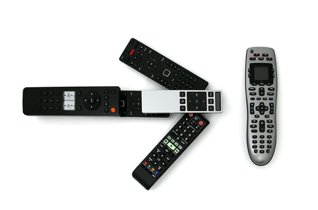 Isolated shot of multiple remotes pointing to one universal remote.