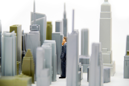 Figurine standing among city sky scrapers, contemplating a real estate investment. Stock Photo