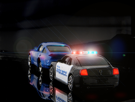Toy police car pulls over sports car.