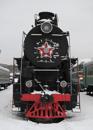old Soviet locomotive at a train station in winter  front view