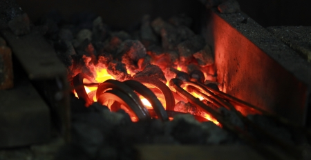 Fire in a blacksmiths forge is heated to red heat for hammering Stock Photo
