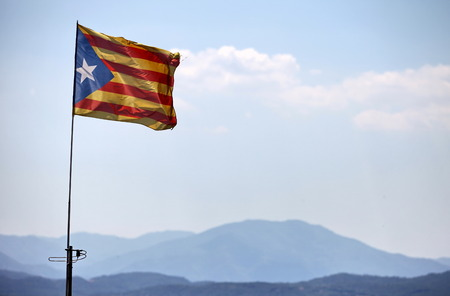Catalan flag with pole blowing in the wind on blue sky with cloud