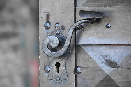 puertas de hierro: antigua puerta de entrada de madera con manija de la puerta antigua