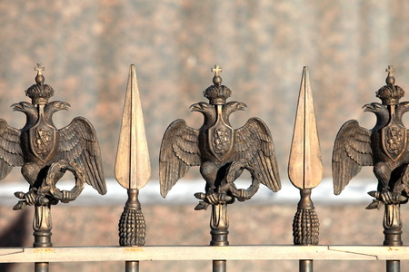 doubleheaded: metal fence with peaks and double-headed eagle Russian Imperial Symbol Stock Photo
