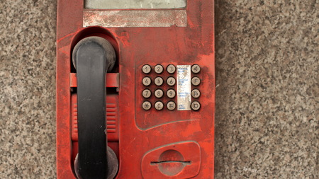 payphone: dirty street payphone on the wall