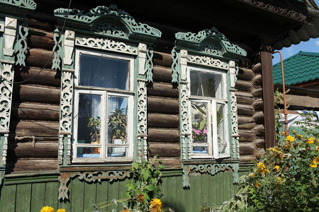log wall: Window decorated with wood carvings on  log wall farmhouse