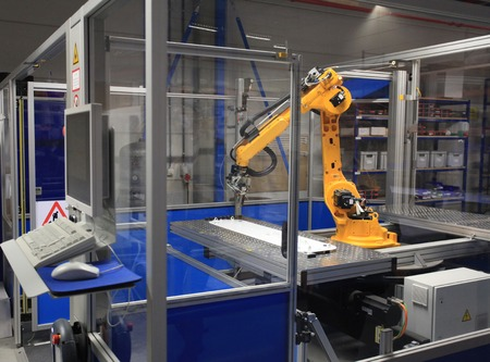 Industrial robotic arm in electronics production line Standard-Bild