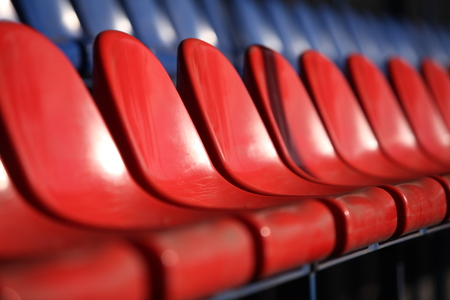 Red chairs bleachers in stadium close to Stock Photo
