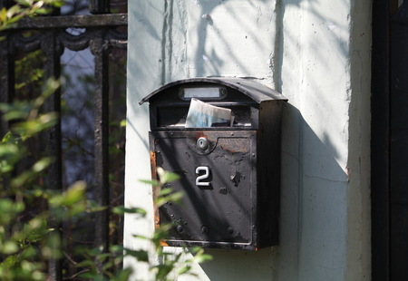 Old mailbox with newspaper on the wall