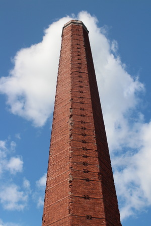 old factory chimney in red brick against the blue sky Stock Photo