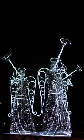 luminous figures of three angels with trumpets at night