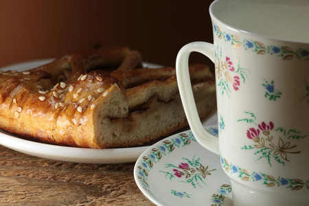 Beautiful white porcelain cup painted with flowers and a piece of sweet cake with sesame seeds Stock Photo