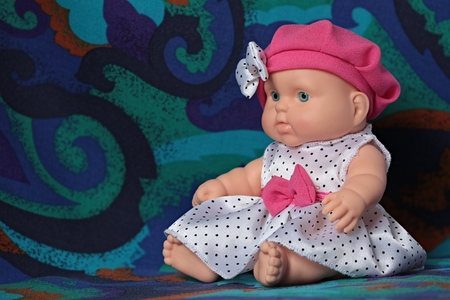 little doll baby in a beret with a bow macro shot