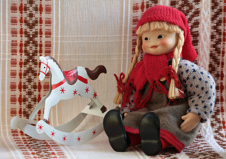 little puppets in national folklore dress Finland  is sitting, beside rocking horse