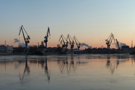 Silhouettes portal cranes reflection on water port St. Petersburg Stock Photo