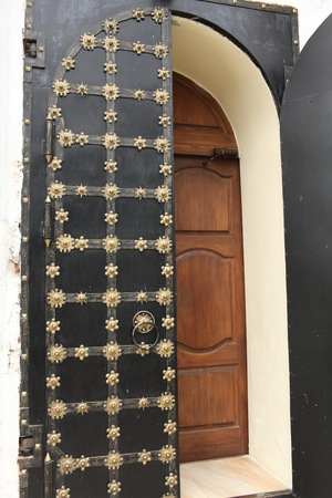 Ancient solid double doors open, decorated gold flowers Stock Photo