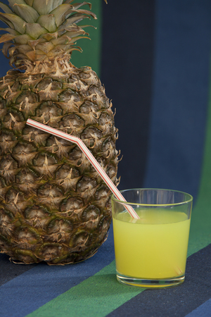 glass of juice with a straw near Pineapple