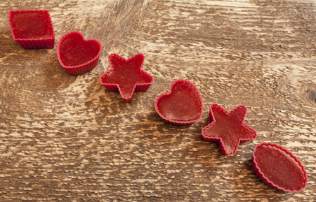 handmade Red marmalade in molds on wooden background flat lay