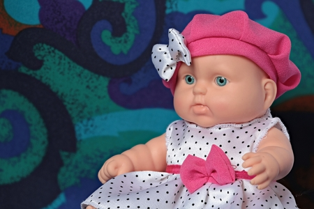 Little doll in a beret with a bow in polka dots