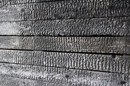 Charred wooden wall after  fire arson, Abstract black background