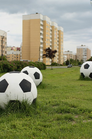 Three big soccer balls on the green lawn cityscape