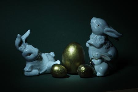 goldene Eier und Familienkaninchen Kreativ beleuchtet, vor einem schwarzen Hintergrund