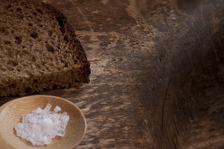 piece rough rye bread with coarse salt on a wooden background, macro shot