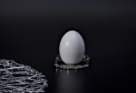 Egg on a silver stand modest breakfast, black background concept luxury, diet, abstinence
