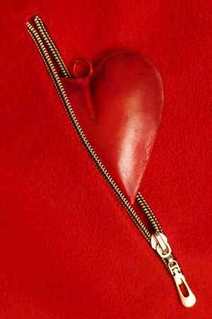 Red heart in red zipper pocket on a red background, wedding or festive concept Standard-Bild
